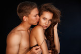 Portrait of young couple in love. Romantic sexy couple over black background. Sensual relations.