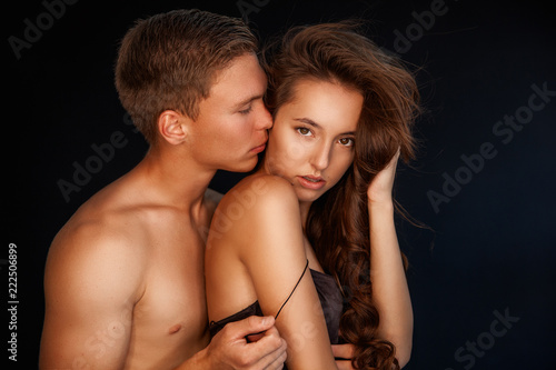 Portrait of young couple in love. Romantic sexy couple over black background. Sensual relations. - 222506899