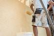 Torso eines Mannes auf Baustelle der eine Wand streicht