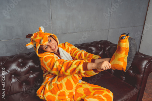 Pajamas for Halloween in the form of a kangaroo. Emotional portrait of a girl on a sofa background. Crazy and funny man in a suit. Clean skin and long hair. Animator for children's parties - 222511832