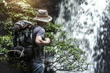 Traveler enjoying with backpack and travel equipment in front of waterfall. Travel lifestyle concept