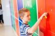 Child boy opening metal school locker.