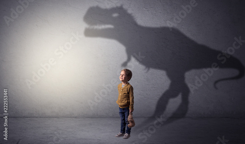 Fototapeta I m dreaming about dinosaurus concept with cute little boy in an empty room