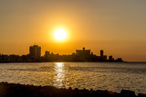 Orange sunset at the sea with buildings in the background in Havana, Cuba