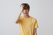 Portrait of desperate unhappy young man with hand on head and braces on teeth in yellow t shirt looks sad and having a headache isolated over white background