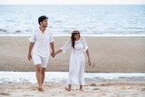 Happy young couple walk on the beach on honeymoon. - 222565673