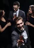 stylish young man raising a glass of wine - 222576812