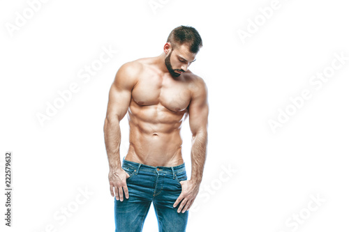 Leinwanddruck Bild bodybuilder posing. Beautiful sporty guy male power. Fitness muscled in blue jeans. on isolated white background.