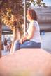 Junge Frau sitzt in urbaner Gegend auf Mauer und blickt dem Sonnenuntergang entgegen, Vitamin D