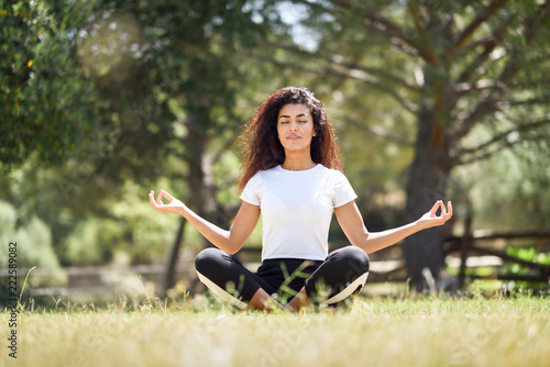 Poster Young Arab woman doing yoga in nature