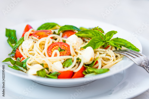Spaghetti caprese - traditional Italian pasta with mozzarella cheese, cherry tomatoes and basil - 222595460