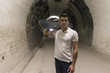 Young 20-25 years old man in tunnel with skateboard. Ambient light image (IMAGE HAVE SOME NOISE)