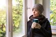 Frau steht an einem Fenster und trinkt ein heißes Getränk, Winter und aufwärmen