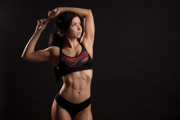 Athletic beautiful brunette sports woman with long hair wearing sport wear posing at camera over black background, showing strong biceps. Sport, Health and Power Concept © alfa27