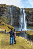 Seljalandsfoss, Iceland - Oct 22th 2017 - Young couple enjoying the Seljalandsfoss fall in a overcast day in Iceland.