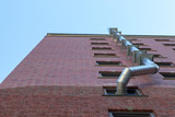 Building wall looking up with silver piping, summer sun. - 222648402