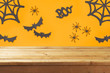 Empty wooden table over Halloween holiday decorations background