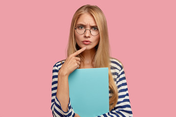 Photo of good looking woman scientist with attentive concentrated gaze, listens with serious expression, analyzes information, dressed in casual striped clothes, isolated over pink background
