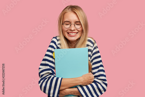 Leinwanddruck Bild Happy overjoyed smiling teenager with blonde hair, keeps textbook closely, laughs at something funny, has break between classes, poses against pink background, dressed in striped sailor sweater