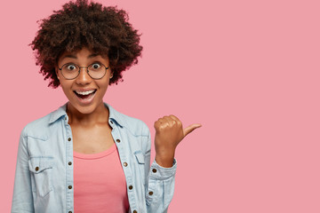 Indoor shot of beautiful African American woman with crisp dark hair, sees something wonderful on right, points with thumb aside, dressed in denim jacket, shows item against pink background.