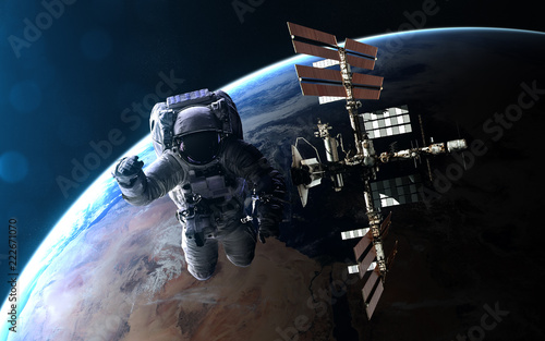 Leinwandbild Motiv Astronaut and ISS on background of Earth in blue rays of Sun. Abstract science fiction. Elements of the image are furnished by NASA