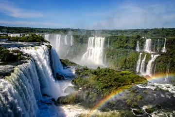 Water cascading over the Iguacu falls with rainbow in foreground in Brazil
