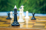 soft focus creative close foreshortening chess black and white figures on wooden classic yellow desk with quadratic marking on unfocused background