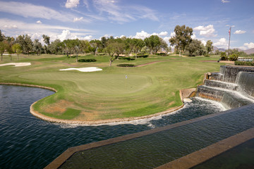 Beautiful Arizona golf landscape scene in Scottsdale with waterfall in foreground and golf green,