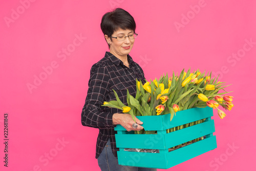 Beautiful middle-aged woman with yellow tulips on pink background. Floristics, holidays and gifts concept - 222681843