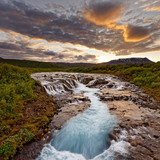 Large waterfall in a wide landscape in the evening light, clouds are illuminated in color, water movement in long exposure - Location: Iceland, Golden circle, Bruarfoss