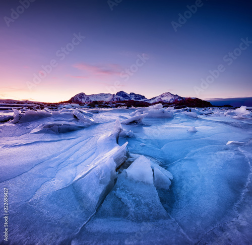 Mountain ridge and reflection on the frozen lake surface. Natural landscape on the Lofoten islands, Norway. Water and mountains during sunset.