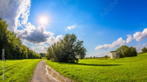 Lato krajobraz z ścieżką przez łąk i niebieskiego nieba z jaskrawym słońcem w tle