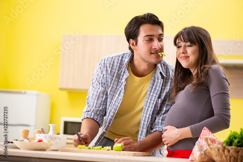 Leinwanddruck Bild Man and pregnant woman preparing salad in kitchen