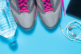 Sport flat lay pink shoes with bottle of water, phone, earphones on blue background with copyspace. Concept healthy lifestyle and diet.