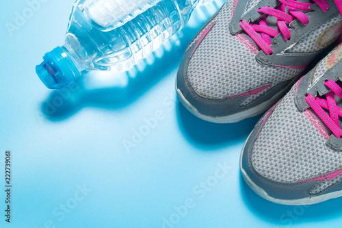 Wall mural Sport pink shoes and bottle of water on blue background with copyspace for your text. Concept healthy lifestyle and diet.