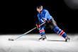 Leinwanddruck Bild - Hockey player with stick turning around skating on ice against black background