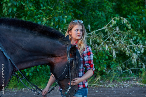 Fototapeta Beautiful girl with long hair on a walk with a horse. Summer cool evening.
