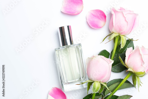 Perfume bottles and rose on white background