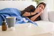 Young woman sneezing nose lying on the sofa at home