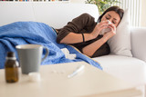 Young woman sneezing nose lying on the sofa at home - 222770889