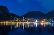 Night view of Lecco reflected on Lake Como with the mountains in the background