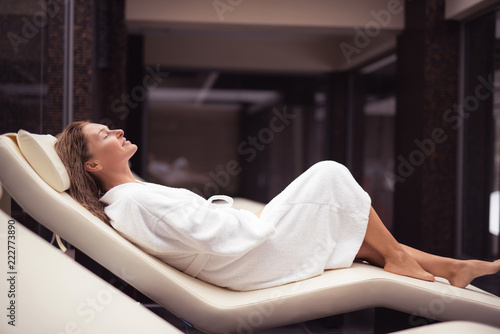 Leinwanddruck Bild Pure pleasure. Side view portrait of charming lady with closed eyes lying on daybed after shower. She is wearing soft white bathrobe and smiling