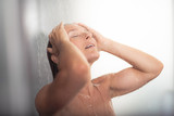 Relief and relaxation. Portrait of attractive wet lady with closed eyes and opened mouth standing under water drops