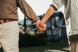 Close up of female hand is kept close to man figure. Twosome standing on lawn fronting house at blurred background - 222785260