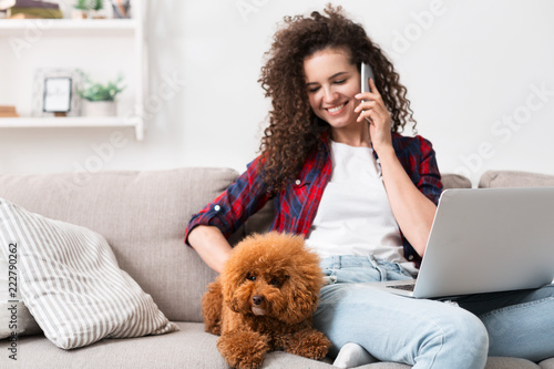 Woman working at home with cute dog - 222790262