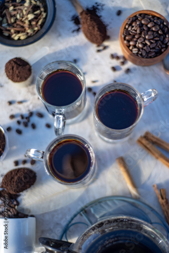 above view of mugs of hot black coffee still life with whole coffee beans, ground coffee, coffee grinder