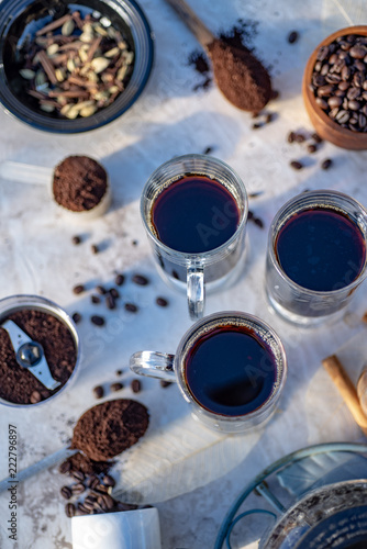 Sticker above view of mugs of hot black coffee still life with whole coffee beans, ground coffee, coffee grinder