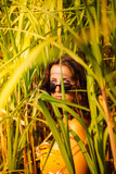 Young woman with sunglasses in a bamboo field