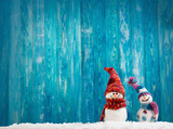 Fototapety little knitted snowmans on soft snow on blue background