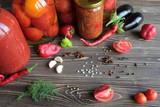 Маринованные помидоры в банках и овощи и пряности на столе.  - 222822467